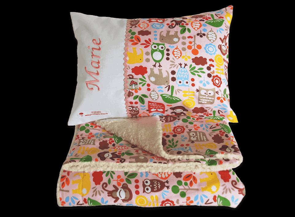 Das Namenskissen und die passende Decke sind mit Eulen, Pilzen, Blättern und anderen Tieren verziert