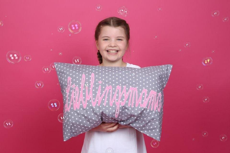 "Antonia hält stolz das Kissen mit der Aufschrift ""Lieblingsmama"""